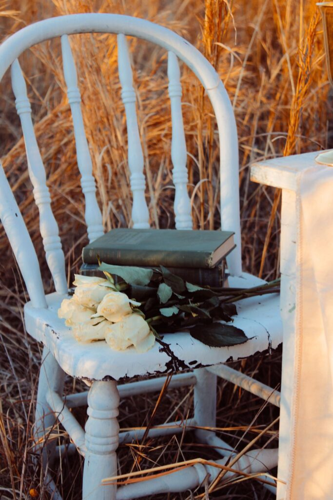 Vintage white chair with roses and stack of green book.