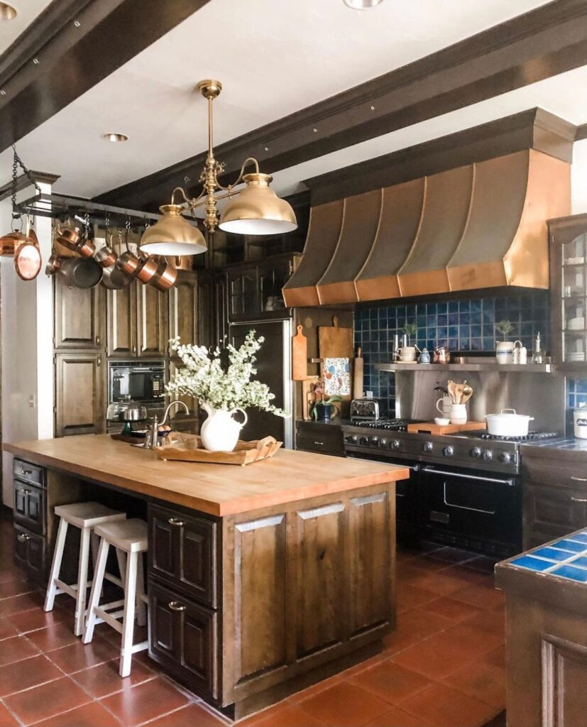 Large country kitchen with copper hood and professional stove.