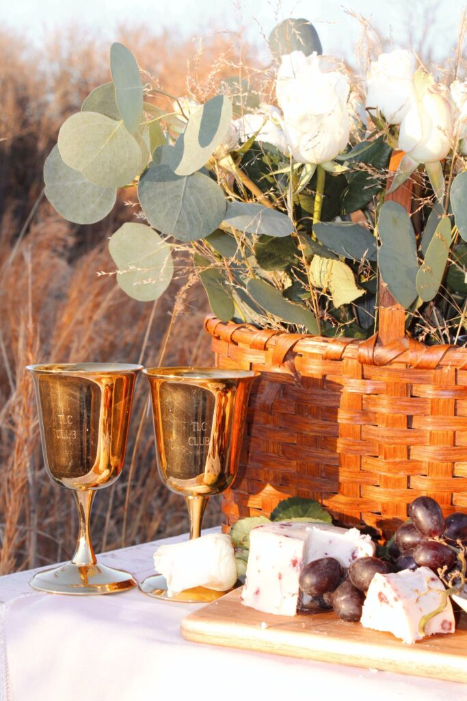 Gold goblets, flowers cheese and grapes.